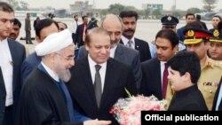 Le président de l'Iran M. Hassan Rohani reçoit un bouquet de fleurs à son arrivée à Nurkhan Airbase, Islamabad, 25 mars 2016