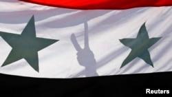 一名阿萨德支持者在叙利亚国旗后面作出胜利手势