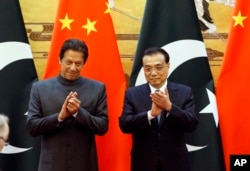 Pakistani Prime Minister Imran Khan, left, and China's Premier Li Keqiang attend a signing ceremony at the Great Hall of the People in Beijing, Nov. 3, 2018.