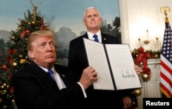 FILE - After signing, U.S. President Donald Trump holds up the proclamation that the United States recognizes Jerusalem as the capital of Israel and will move its embassy there, during an address from the White House in Washington, U.S., Dec. 6, 2017.