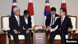 South Korean Defense Minister Han Min-Koo (R) talks with Japanese Defence Minister Gen Nakatani