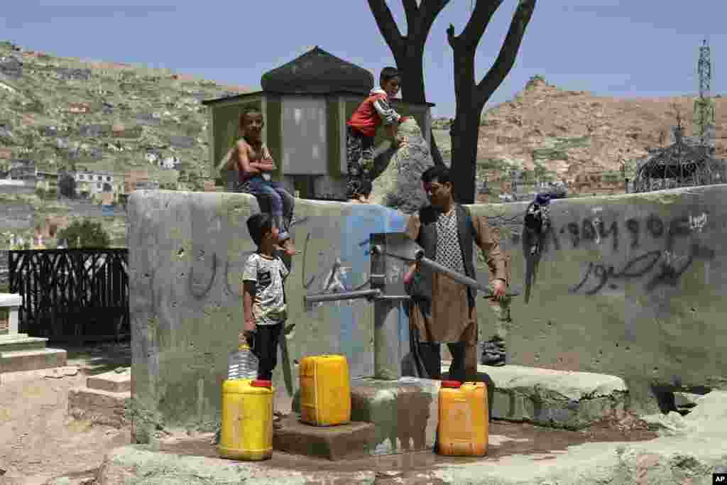 A man and his children collect water from a public water pump in Kabul, Afghanistan.