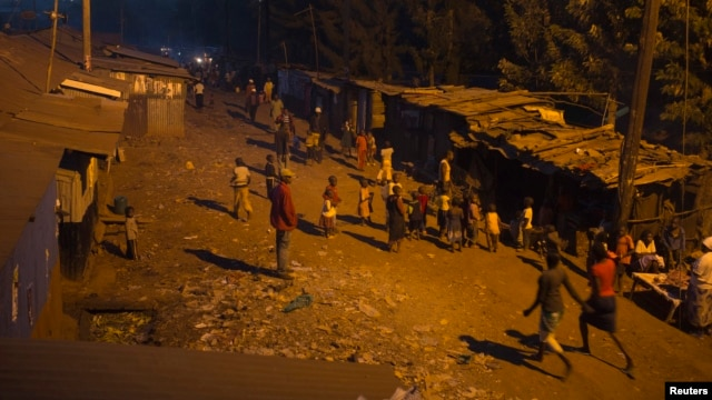 People walk back home during early evening at the Kangemi slum in Kenya's capital Nairobi, February 28, 2013.