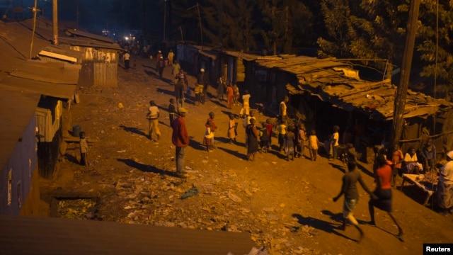 People walk back home during early evening at the Kangemi slum in Kenya's capital Nairobi, February 28, 2013.