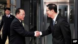 Dans cette photo fournie par le ministère de l'Unification de la Corée du Sud, le vice-ministre coréen de l'Unification Chun Hae-sung, à droite, serre la main de la délégation nord-coréenne Jon Jong Su avant leur rencontre à Panmunjom dans la zone démilitarisée de Paju, le 17 janvier 2018