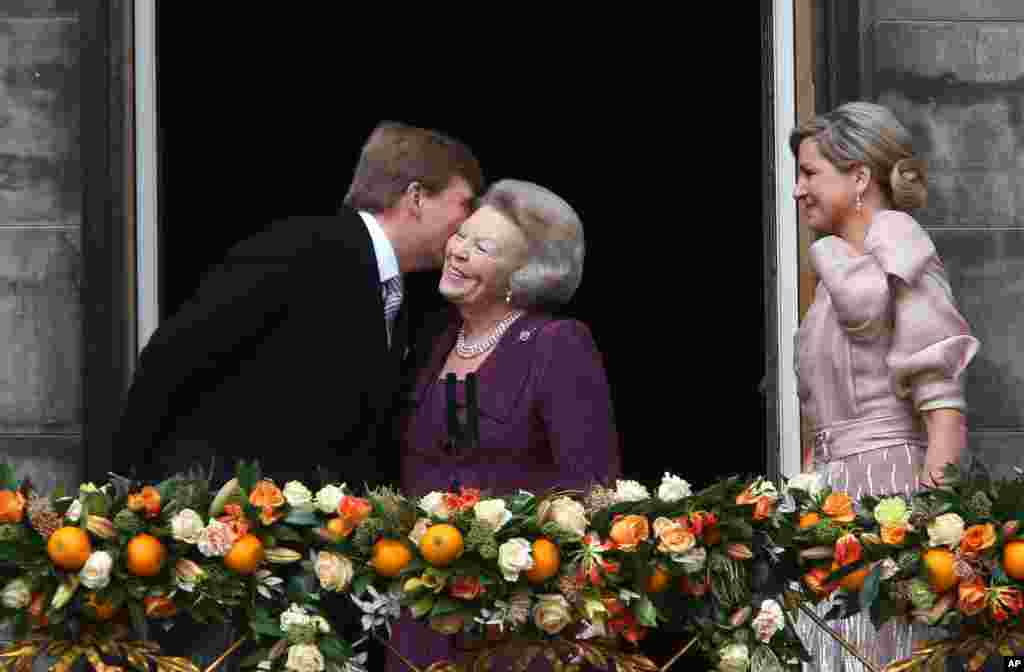 Dutch King Willem-Alexander kisses his mother Princess Beatrix as his wife Queen Maxima looks on from the balcony of the Royal Palace in Amsterdam.