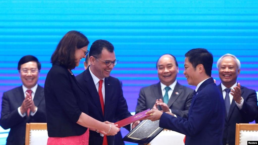 Thành viên hội đồng thương mại EU Cecilia Malmstrom (trái) và Bộ trưởng Công Thương Việt Nam Trần Tuấn Anh trao đổi tài liệu tại lễ ký hiệp định thương mại EU-Việt Nam ở Hà Nội hôm 30/6/2019. Nghị viện châu Âu sẽ bỏ phiếu bầu về hiệp định này vào ngày 21/1.