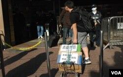 有示威者拖著寫上標語的手拉車,在上水港鐵站抗議水貨客影響秩序
