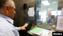 FILE - A man has his fingerprints electronically taken while taking part in a visa application demonstration