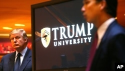FILE - Donald Trump listens as Michael Sexton introduces him to announce the establishment of Trump University at a press conference in New York, May 23, 2005. Sexton was a co-founder of the business education company.