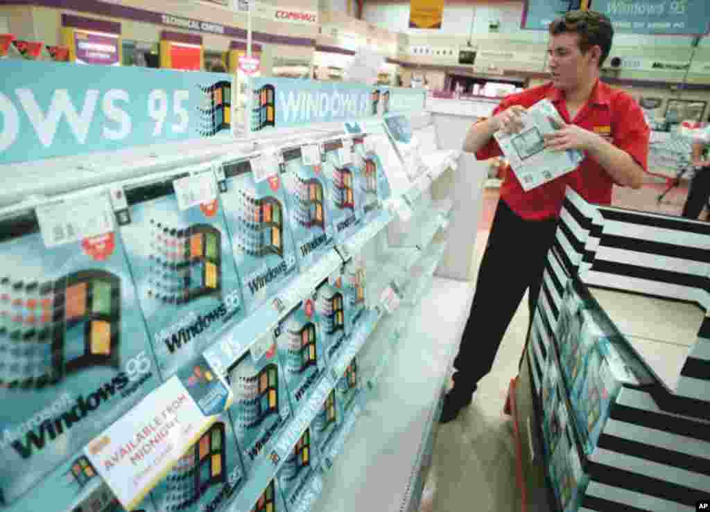 A worker packs the shelves of the computer shop PC World, at Croydon in south London, Aug. 23, 1995, with copies of the Microsoft Windows 95 computer package.
