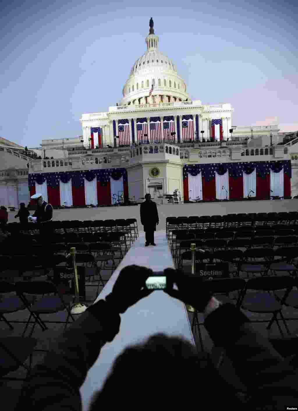 Guests at the Inauguration of the U.S. President Barack Obama take pictures before sunrise at the U.S. Capitol in Washington, January 21, 2013