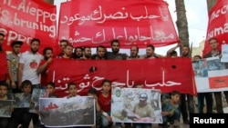 """People hold banners during a sit-in in solidarity with the people of Aleppo in Idlib, Syria, May 4, 2016. The banner reads: """"Oh, Aleppo, your victory is promised no matter how many crowds they bring to you."""""""