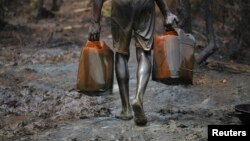 A man carries oil canisters at an illegal refinery site in Nigeria's oil state of Bayelsa in this November 27, 2012, file photo.