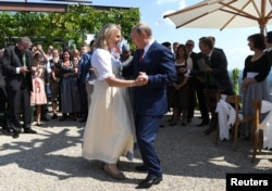 Austria's Foreign Minister Karin Kneissl dances with Russia's President Vladimir Putin at her wedding in Gamlitz, Austria, Aug. 18, 2018.