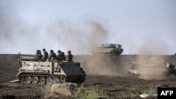 An Israeli Armored Personnel Carrier (APC) and Merkava tanks maneuver during a drill in the Israeli annexed Golan Heights near the border with Syria on May 6, 2013.
