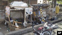 A man inspects the wreckage following a suicide bomb attack on a street in Jalingo, Nigeria, April 30, 2012.