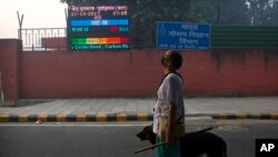 An Indian looks at the air quality level board outside India Meteorological Department, which shows condition of air as severe post during Diwali festival, in New Delhi, Oct. 20, 2017.