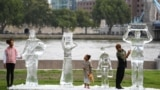 Children pose by ice sculptures depicting people collecting water by charity Water Aid to show the fragility of water and the threat posed by climate change on September 15, 2021 in London.