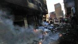 مصریان در اطراف ساختمانی در محله ایمبابه که در زد و خورد میان مسیحیان و مسلمانان به آتش کشیده شد جمع شده اند - قاهره - ۸ مه ۲۰۱۱