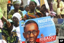 A supporter holds a poster campaigning for former anti-graft chief Nuhu Ribadu of the Action Congress of Nigeria