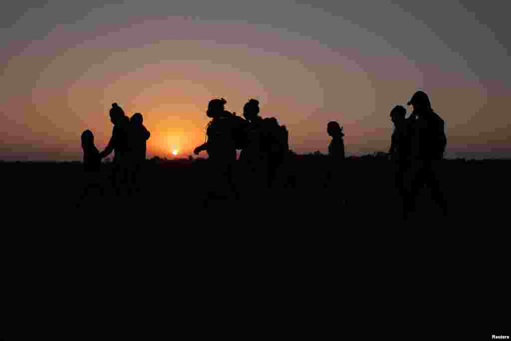 The sun rises as asylum-seeking migrant families from Honduras and El Salvador walk towards the border wall after crossing the Rio Grande River into the United States from Mexico on a raft, in Penitas, Texas.
