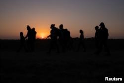 Porodice migranata iz Hondurasa i Salvadora koračaju prema graničnom zidu nakon što su splavom u Penitasu u Texasu iz Meksika prešle rijeku Rio Grande.