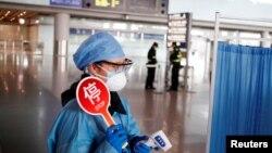 身穿防護服的工作人員在北京機場的抵達大廳檢測旅客體溫。(2020年3月4日)