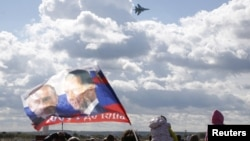 A spectator waves a flag depicting images of Russian President Vladimir Putin (L) and Prime Minister Dmitry Medvedev as a Sukhoi SU-34 fighter-bomber performs during the MAKS International Aviation and Space Salon in Zhukovsky outside Moscow, Russia, Aug. 30, 2015.