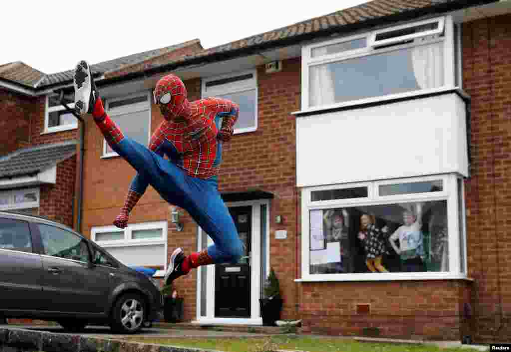 Jason Baird dressed as Spiderman exercises to cheer up local children in Stockport as the spread of the coronavirus disease (COVID-19) continues in Britain.