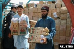Para pekerja membongkar truk bermuatan kotak buah delima dari Afghanistan, di titik persimpangan 'Gerbang Persahabatan', di Chaman, Pakistan, kota perbatasan Pakistan-Afghanistan, 7 September 2021. (REUTERS/Saeed Ali Achakzai/File Foto)