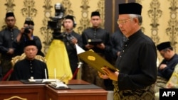 Malaysia's Prime Minister Najib Razak (R) reads his oath declaration in front of Malaysia's King Abdul Halim Mu'adzam Shah as he is sworn in for his second term as prime minister, May 6, 2013.