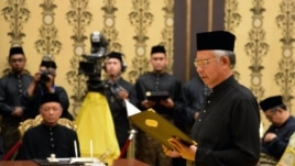 Malaysia's Prime Minister Najib Razak (R) reads his oath declaration as he is sworn in for his second term as prime minister, May 6, 2013.