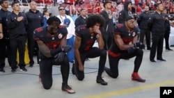 San Francisco 49ers outside linebacker Eli Harold (58), quarterback Colin Kaepernick (7) and safety Eric Reid (35) kneel during the national anthem before an NFL football game Oct. 6, 2016.