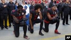 Jugadores de los San Francisco 49ers Eli Harold (58), mariscal de campo Colin Kaepernick (7) y Eric Reid (35) se arrodillan durante el himno national antes de un juego de la NFL, el 6 de octubre de 2016.