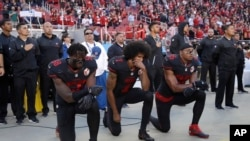 FILE - San Francisco 49ers outside linebacker Eli Harold (58), quarterback Colin Kaepernick (7) and safety Eric Reid (35) kneel during the national anthem before an NFL game, Oct. 6, 2016.