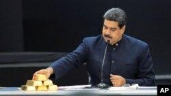 El presidente de Venezuela Nicolás Maduro toca una barra de oro mientras habla durante una reunión con sus ministros en el palacio de Miraflores en Caracas, Venezuela, el 22 de marzo del 2018.