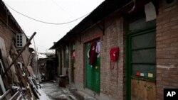 """Quần áo treo bên ngoài lối vào một ngôi nhà gạch, được biết đến như là một """"nhà tù đen"""" ở Bắc Kinh."""
