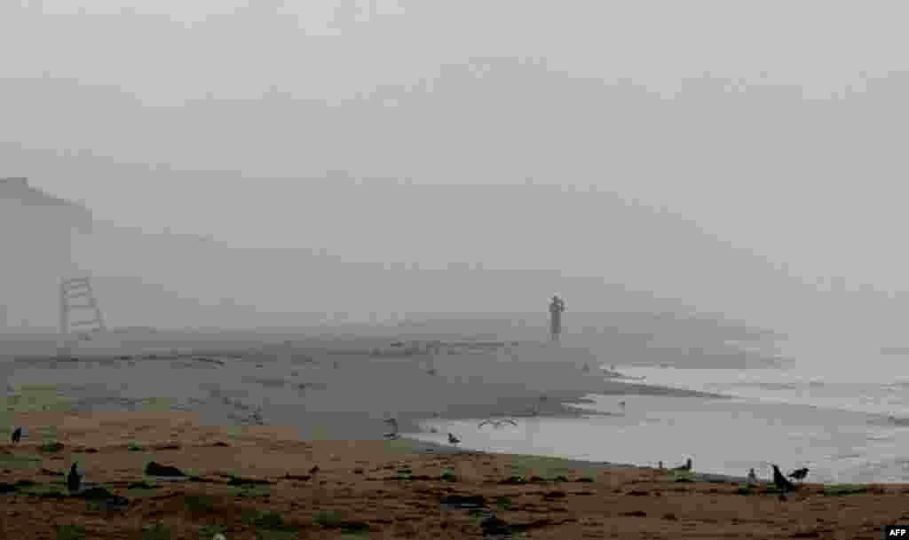 26 tháng 8: Vẫn còn một du khách đi lang thang trên bãi biển North Carolina, dù đã có lệnh di tản khi bão Irene đánh vào tiểu bang này hôm thứ Sáu. (AP Photo/Gerry Broome)