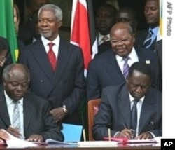 President Kibaki (l) and Prime Minister Raila Odinga (r) signs the agreement that led to the coalition government following the 2007 post-election violence.