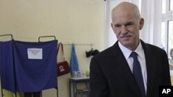 Greek Prime Minister George Papandreou receives an envelope to vote during the municipal and regional elections in Athens, 7 Nov. 2010.