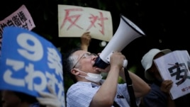 A man shouts slogans over a public-address system during a protest outside the Japanese prime minister's office, July 1, 2014.