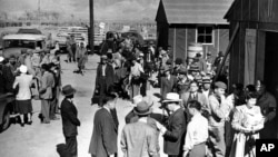 FILE - The first arrivals at the Japanese evacuee community established in Owens Valley in Manzanar, Calif., part of a vanguard of workers from Los Angeles, March 23, 1942. Roughly 120,000 Japanese immigrants and Japanese-Americans were sent to camps that dotted the West because the government claimed they might plot against the U.S.