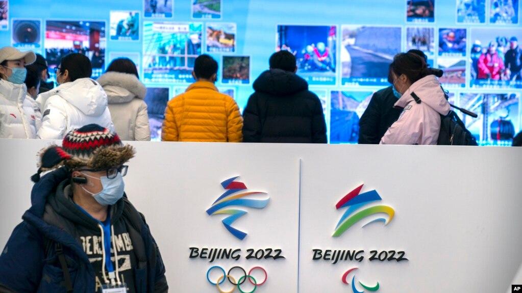 资料照片:在北京延庆冬奥会场馆游客中心,一名记者戴着口罩观看展览。(2021年2月5日)