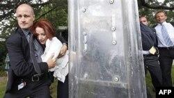 Nữ Thủ tướng Úc Julia Gillard được các cận vệ và cảnh sát đưa qua khỏi đám đông biểu tình một cách an toàn hôm 26/1/12