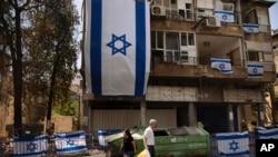 Stanovnici Ramat Gana u Izraelu prolaze pored stambene zgrade koju je pogodila raketa ispaljena iz pojasa Gaze, 21. maja 2021.