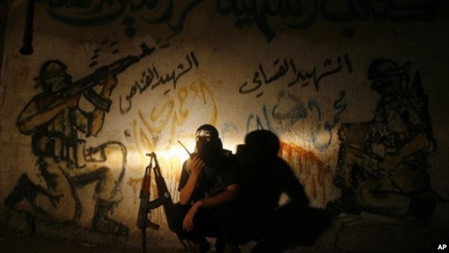 A Palestinian militant member of the Qassam Brigades, Hamas' armed wing, talks on a walkie-talkie at Rafah refugee camp, southern Gaza strip, August 21, 2011