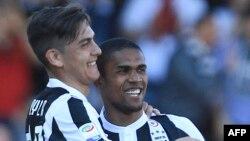 L'attaquant brésilien de la Juventus, Douglas Costa, à droite, congratule l'attaquant argentin de la Juventus Paulo Dybala après un but lors du match de football contre le Benevento Calcio au stade Ciro Vigorito, Italie, 7 avril 2018.
