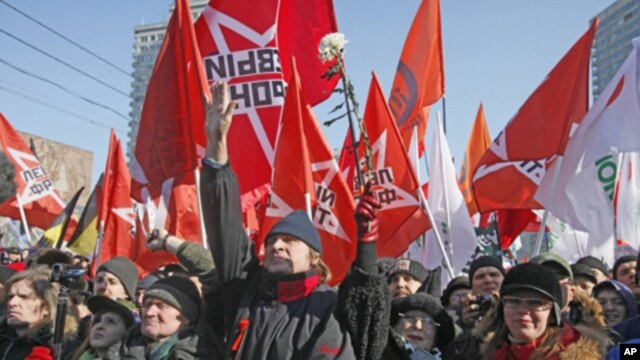 Opposition protesters with their flags shout anti-Putin's slogans as they gathered in the center of Moscow during a rally, Saturday, March 10, 2012.