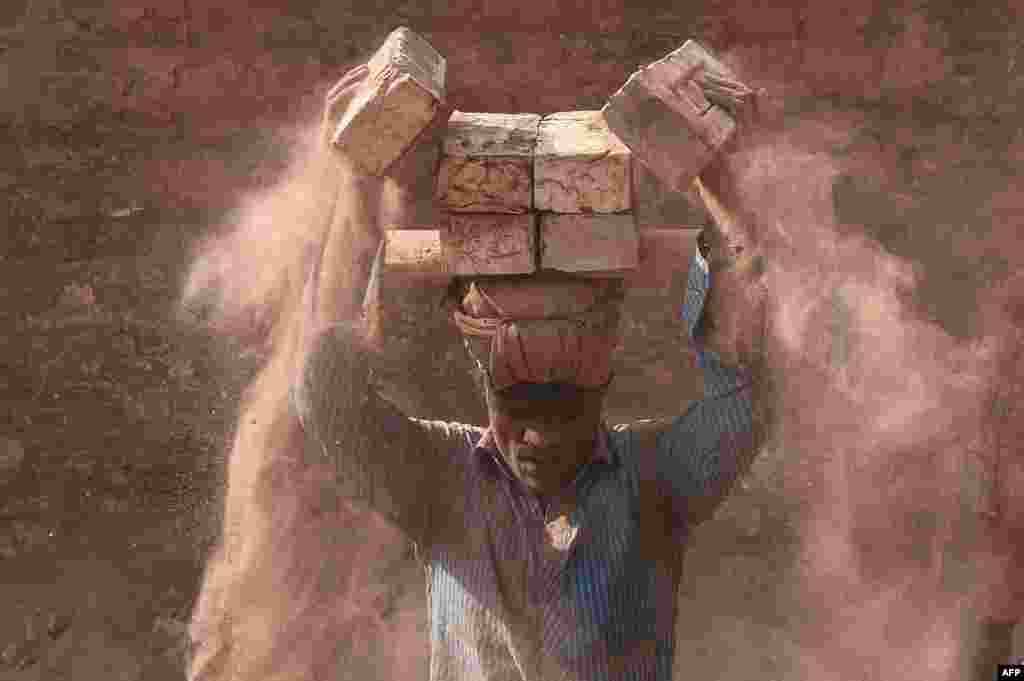 A man carries bricks in a brickfield in Saver on the outskirts of Dhaka, Bangladesh.